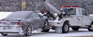 Tow truck towing a car from the side of the word in winter